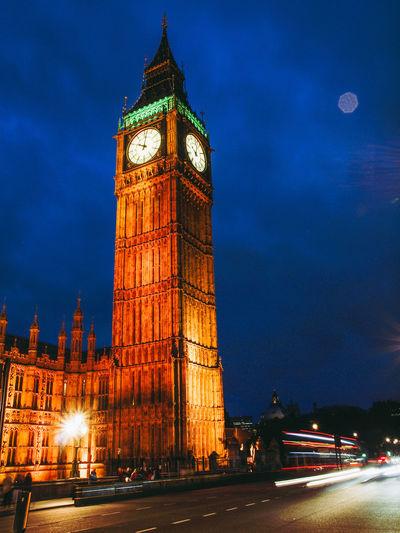 Illuminated clock tower against sky at night