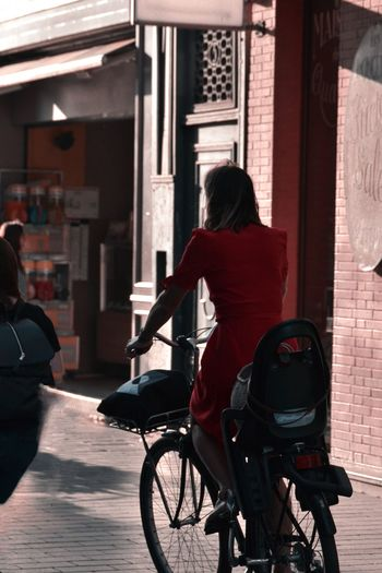 Rear view of woman with bicycle on street in city