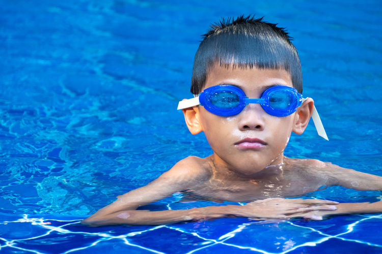 Portrait of asian boy ware a blue glasses and floating at the corner of swimming pool and blue refreshing water Boy Face Goggles Blue Swim Swimming Pool Kid Asian  Relaxing Play Childhood Happiness Glasses Child Healthy Fun Water Smile Cool Still Cute Summer Splash Arms Sport Victory Gesture person Outdoor Up Active Holiday Vacation Excited Fit Playing Activities Up Enjoy Lifestyle Relax Emotion Showing Close Swimmer Portrait Wet Young