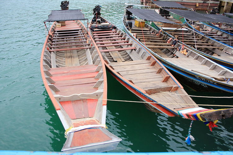 High angle view of longtail boats moored at harbor