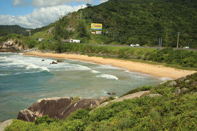 Scenic View Of Beach Against Green Mountain