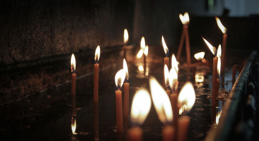 Prayer candles in a small church in Greece. Candles Church Religion And Tradition Belief Candle Candlelight Darkart darkness and light Flame Glowing Illuminated Place Of Worship Prayer Religion Selective Focus Spirituality