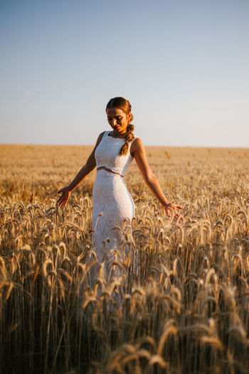 Bride standing amidst cereal plants on agricultural field