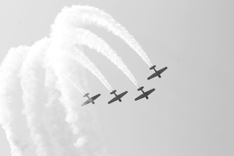 Low Angle View Of Airshow Against Cloudy Sky