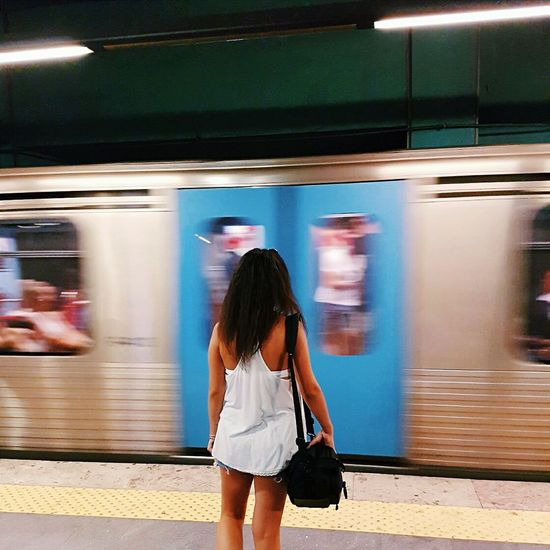 Rear view of woman standing by train at subway station