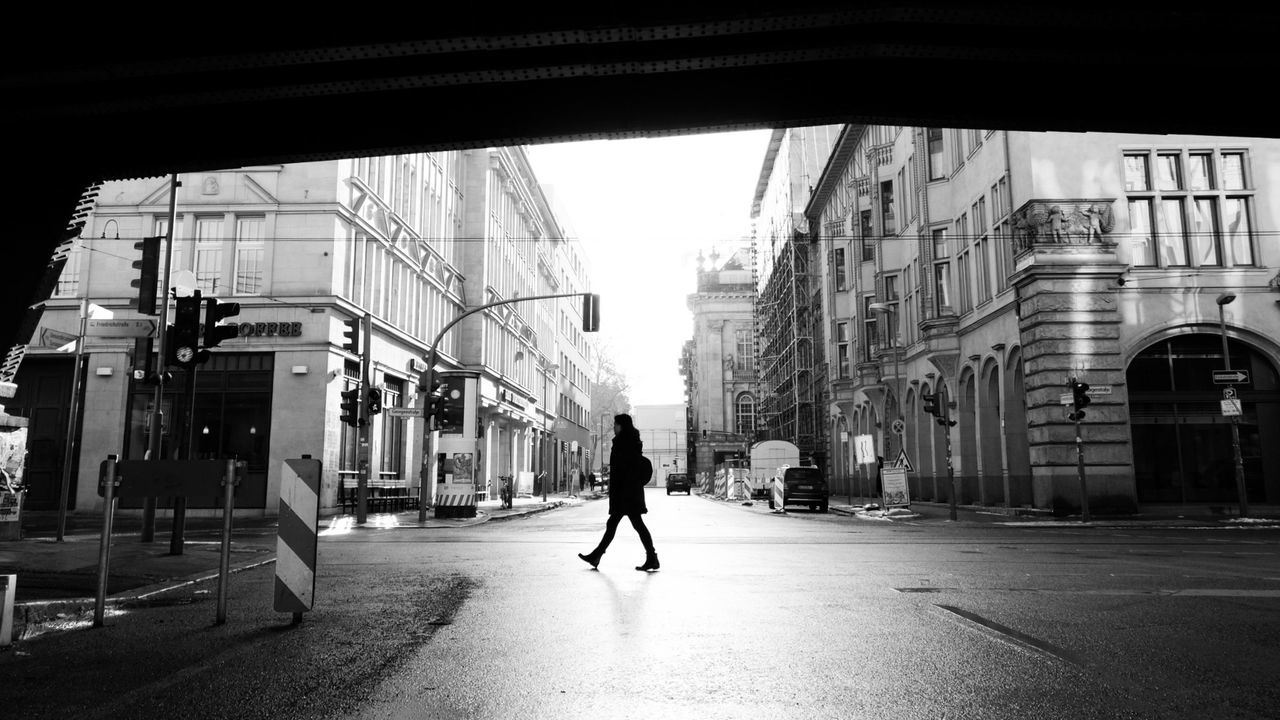 Silhouette Of Woman Crossing City Road