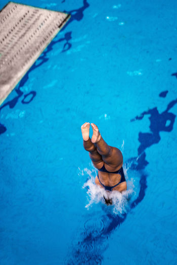 Female Diver Jumping Into The Pool Diving Diver Swimming Pool Woman Water Sport Training Competition Young Exercising Diving Board Board Above Action Swimwear Blue Activity Muscular Build Extreme Sports Caucasian Ethnicity Athlete Jump Jumping Splashing Surface