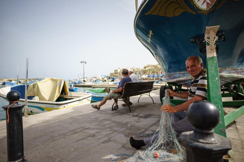Fischer beim Flicken seines Netzes, Marsaxlokk, Malta Marsaxlokk Clear Sky Fisher Net Fisherman Men Nautical Vessel Net Outdoors Real People