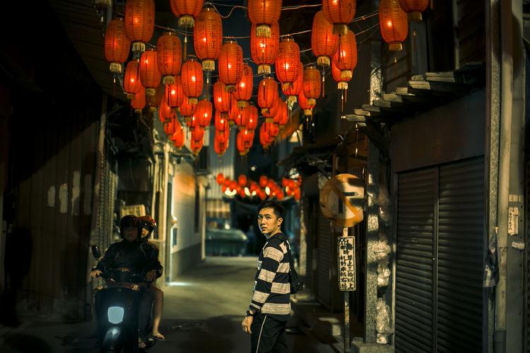 Illuminated lanterns hanging amidst buildings at night