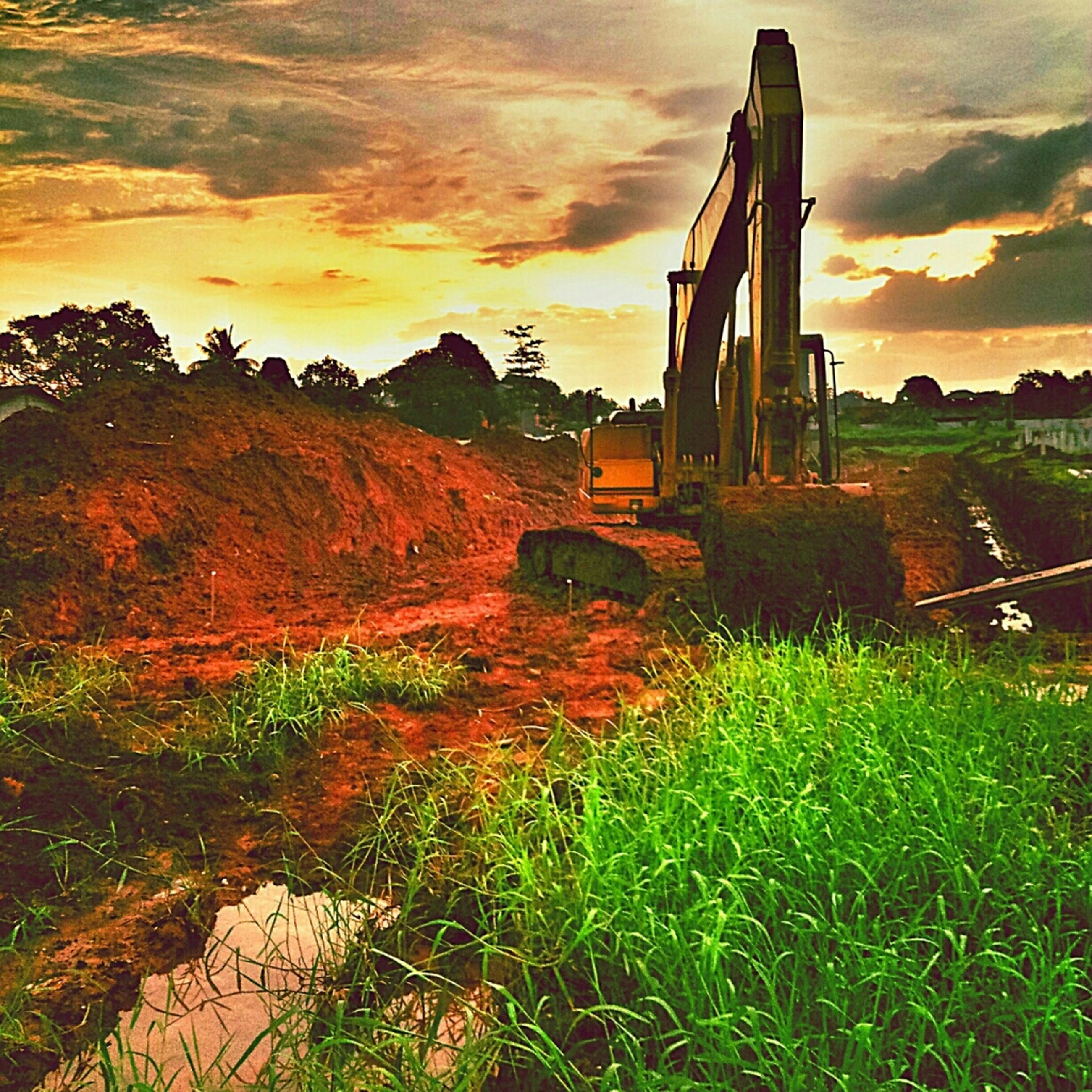 sky, architecture, built structure, sunset, grass, cloud - sky, building exterior, field, cloudy, orange color, cloud, landscape, nature, grassy, plant, tranquility, no people, outdoors, beauty in nature, tranquil scene