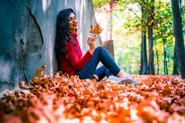 Woman sitting on leaves in park during autumn