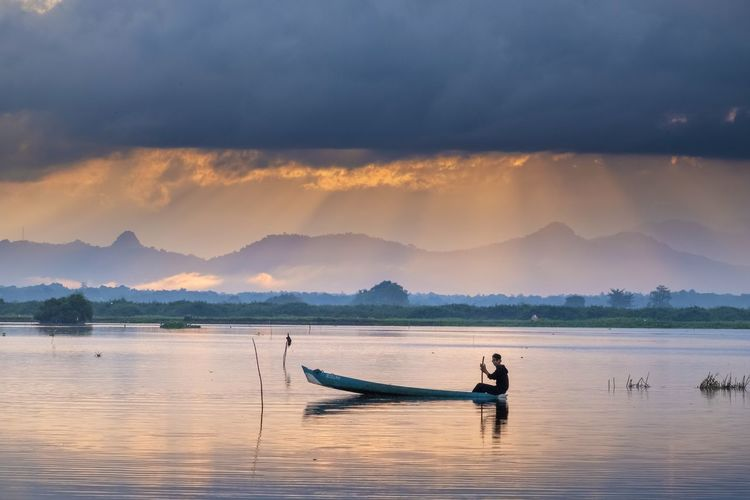 Man on boat in lake against sky during sunset