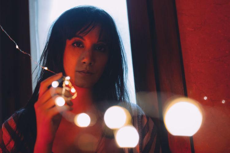 Portrait of woman holding illuminated lighting equipment