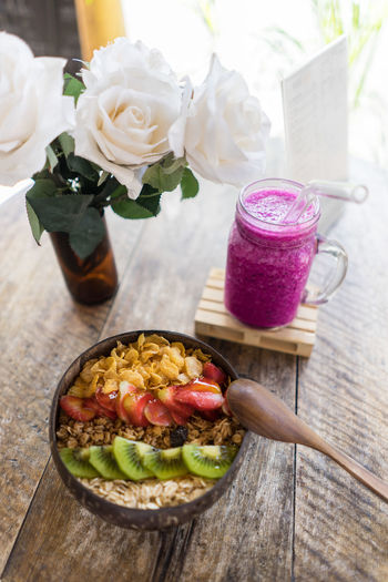 Beauty In Nature Close-up Drink Flower Flower Head Flowering Plant Food Food And Drink Freshness Glass Healthy Eating High Angle View Indoors  Nature No People Plant Ready-to-eat Refreshment Smoothie Still Life Table Wellbeing Wood - Material