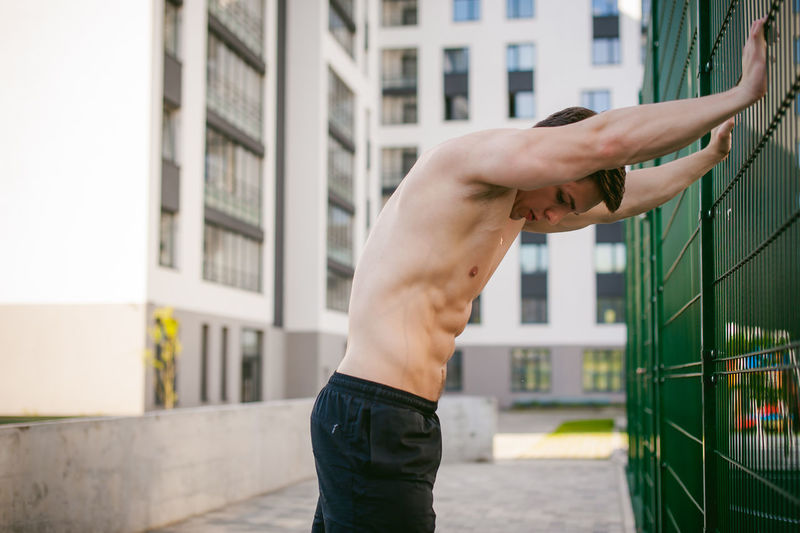 Architecture Building Exterior Built Structure City Close-up Day Exercising Focus On Foreground Healthy Lifestyle Human Hand Lifestyles Men Muscular Build One Person Outdoors People Real People Shirtless Sky Strength Fresh On Market 2018