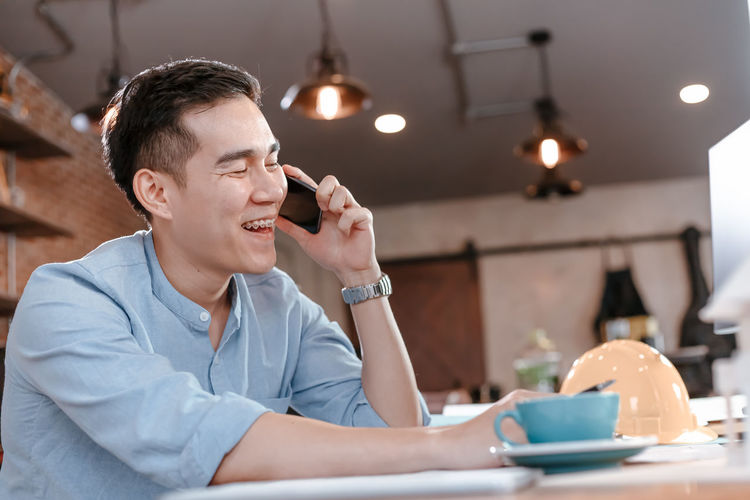 Man using mobile phone while sitting on table