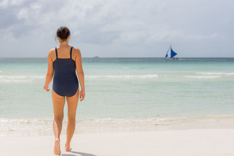 Rear View Full Length Of Woman Standing On Shore At Beach Against Sky