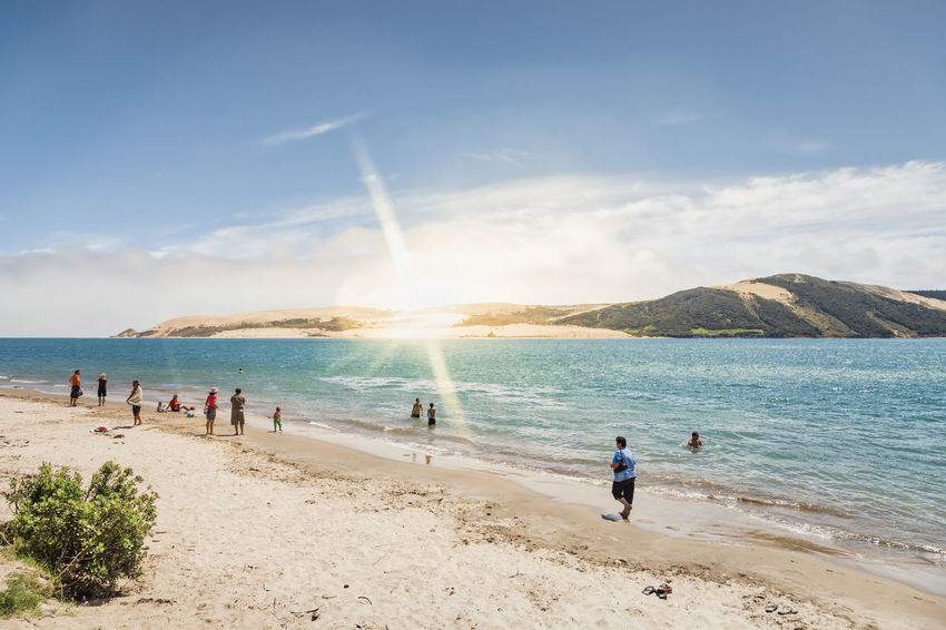 Beach life on a pristine beach in Omapere, North Island, New Zealand. In the background the giant sand dunes of Niua. Beach Life Beach Photography Coastline Hokianga Harbour Landscape_Collection New Zealand Beauty New Zealand Scenery Omapere Panorama Relaxing Sunlight Vacations Beach Beachphotography Landscape Lens Flare New Zealand North Island Opononi People Sand Sand Dune Sea Sunray Water