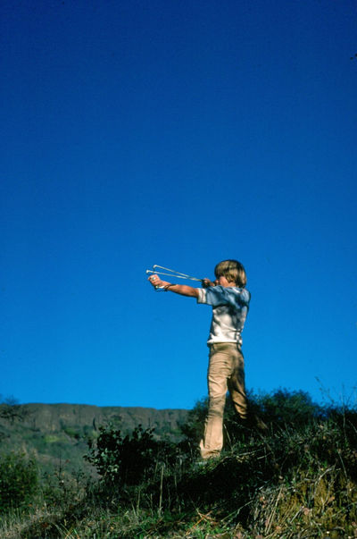 playing with sling shot Adventure Art Beauty In Nature Blue Boy Clear Sky Day Grass Grassy Green Color Hill Landscape Low Angle View Nature Outdoors Play Sky Sling Shot Tranquil Scene Tranquility