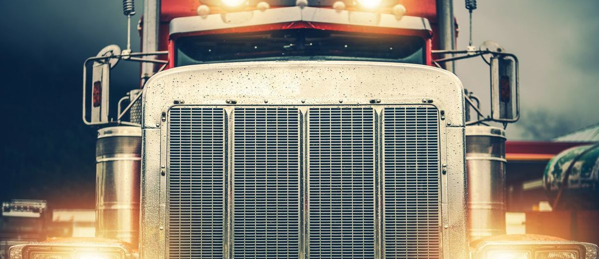 Shiny American Semi Truck on a Road. Large Chromed Grill Front View in Wide Format. Trucker on the Road. Trucker Trucking Front View Automotive Transportation Mode Of Transportation Outdoors Headlights Semi Truck Transportation Transport Cargo Shipping