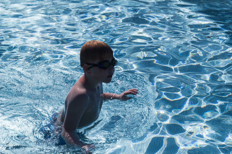 High angle view of shirtless boy in swimming pool