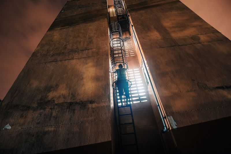 Low Angle View Of Man Standing On Metallic Ladder