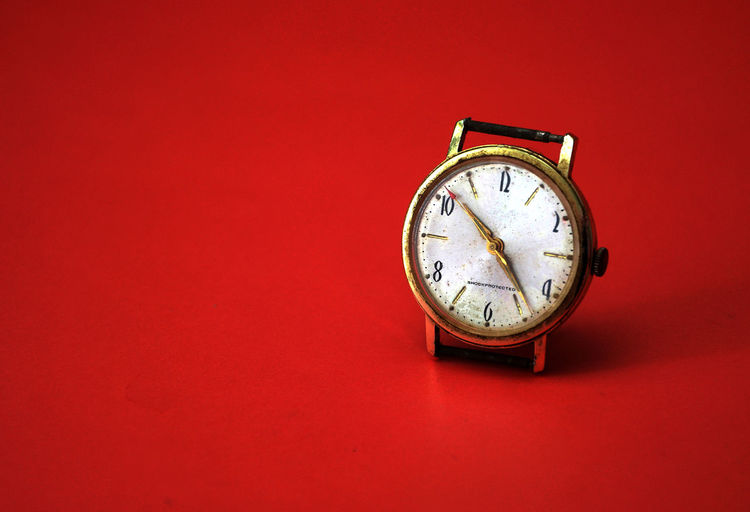 Close-up of antique clock against red background