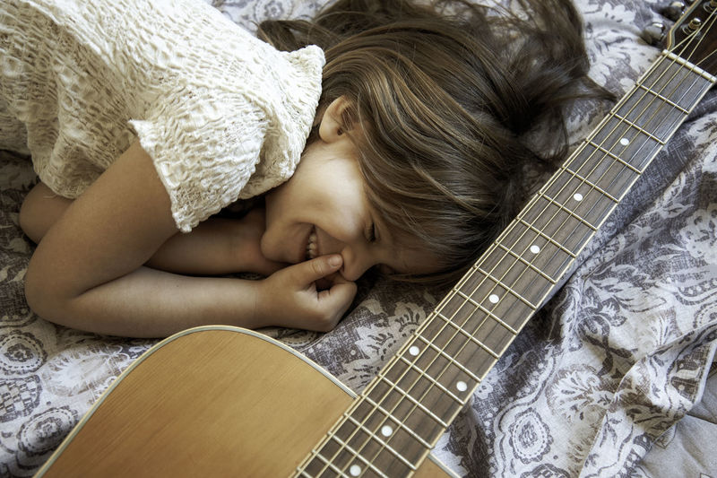Smiling girl lying on bed by guitar at home