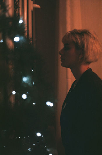 Side view of young woman looking at christmas tree at home