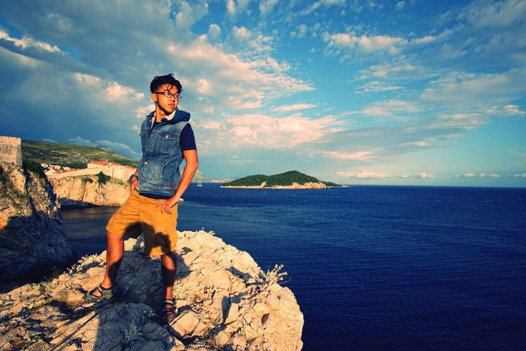 Full length of man standing on rock formation by sea against sky