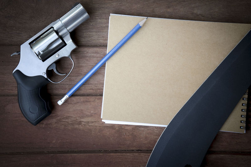 Directly above shot of pistol and knife with book on table