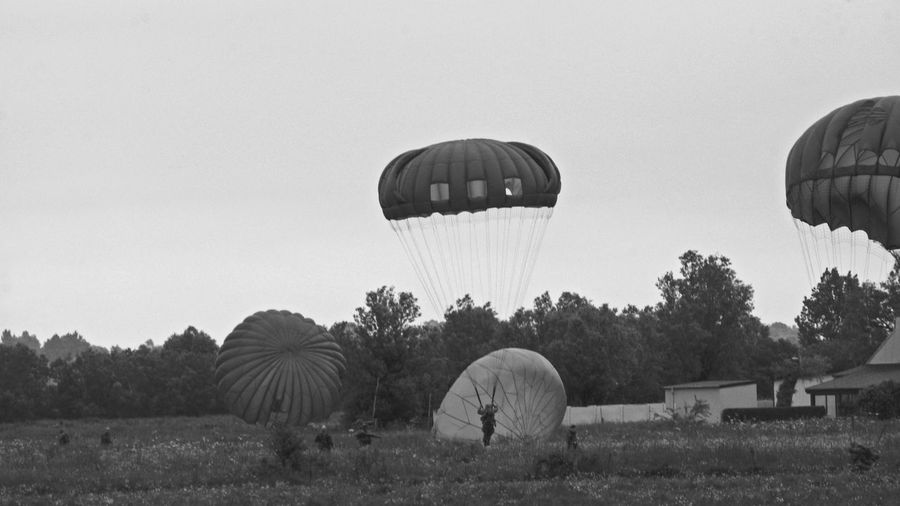 Military soldiers landing on field with parachute against sky