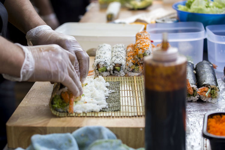 Midsection of person preparing sushi on table