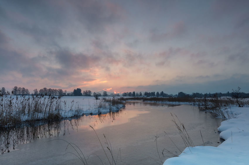Sunrise with cloudy sky at Ach close to Uffing, Staffelsee, Bavaria, Germany Ach Bavaria Blaues Land Nature Staffelsee Tranquility Winter Cloud - Sky Cold Fluss Fozen Frozen Water Germany Moor  Moss No People Red Clouds Reed River Sky Snow, Sunrise Sunrise_sunsets_aroundworld Tranquil Scene Wide Angle