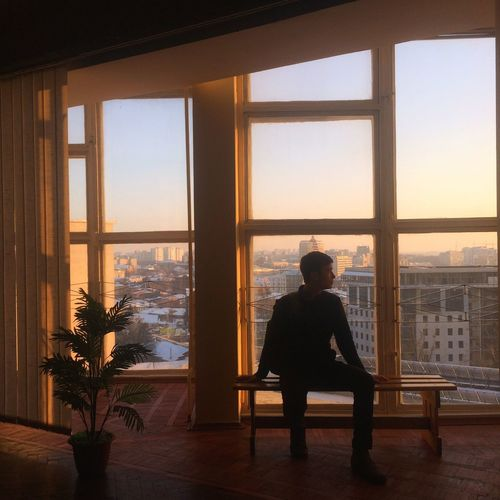 Man sitting on bench against windows during sunset