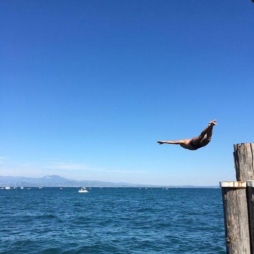Full length of man diving in sea against blue sky