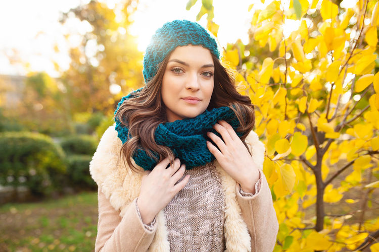 Portrait Of Beautiful Young Woman In Warm Clothing Standing Against Autumn Tree