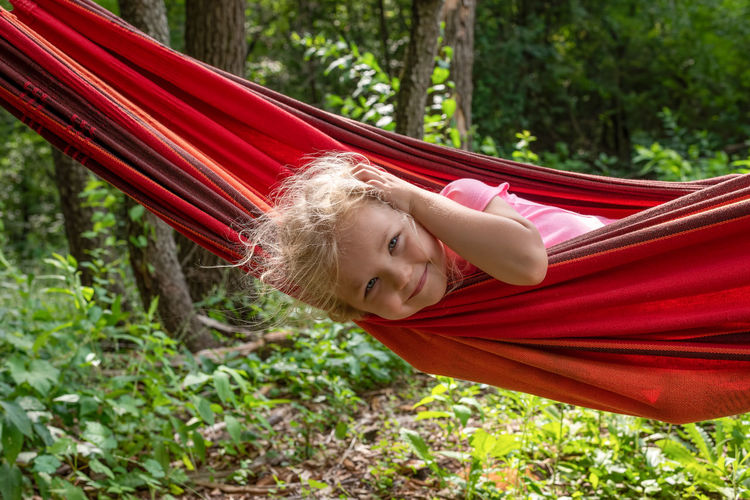 Portrait of smiling woman relaxing on hammock in forest