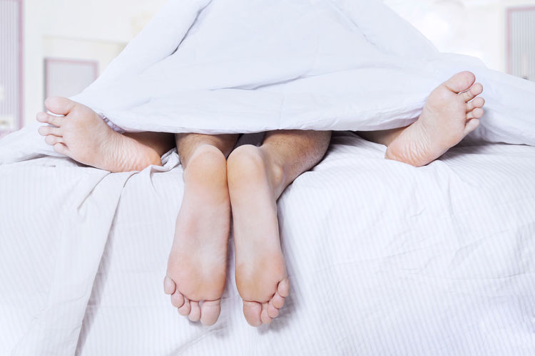 Low section of couple lying on bed