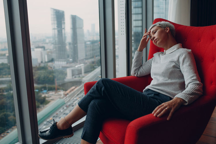 Woman looking through window while relaxing on armchair