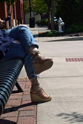 Low section of woman sitting on bench in city