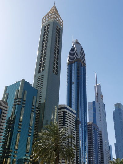 Skyscrapers (Evor Hotel second from left) on Sheik Zayed Road, Dubai, United Arab Emirates 2019 Dubai UAE 2019 Sheik Zayed Road Blue Sky Low Angle View City Tall - High No People Palm Tree Skyscrapers Towers Tower Blocks Steel And Glass Structures Modern Design Modern Architecture Financial District  Cityscape Building Facades Sunlight And Shade Full Frame Composition Outdoor Photography Architecture Tourist Destination