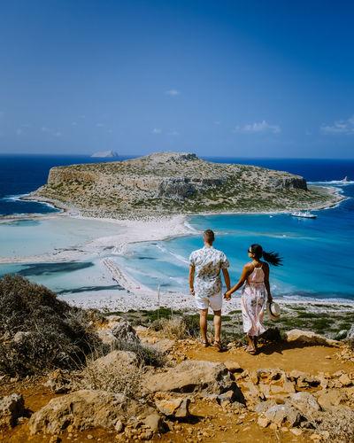 Couple standing on beach against sky