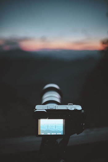 Close-up of camera photographing against sky during sunset