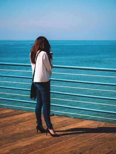 Rear view of woman standing on promenade by sea against sky