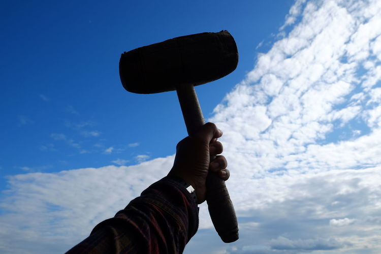 Low angle view of person holding wooden hammer against sky
