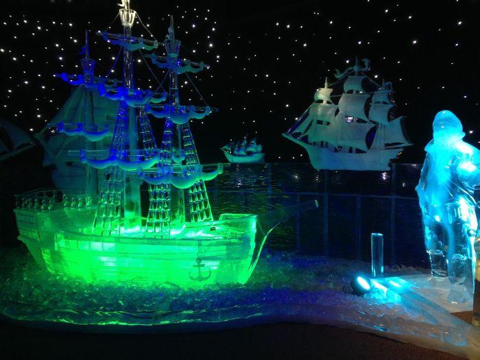 Digital composite image of illuminated lights over sea at night