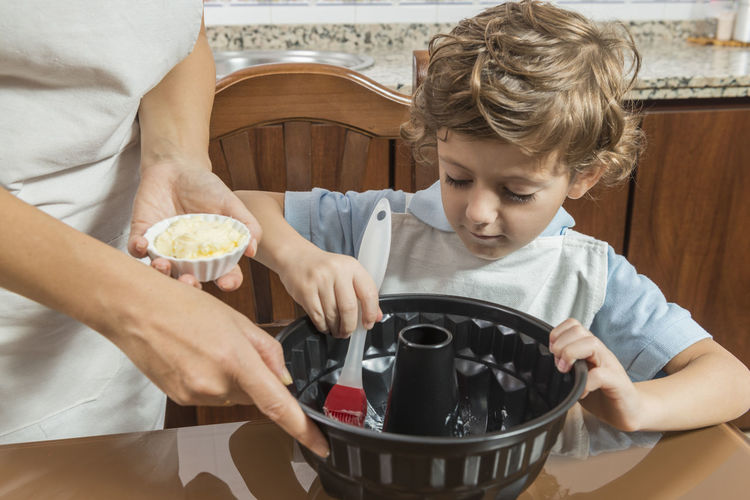 Midsection of mother preparing food with son at home