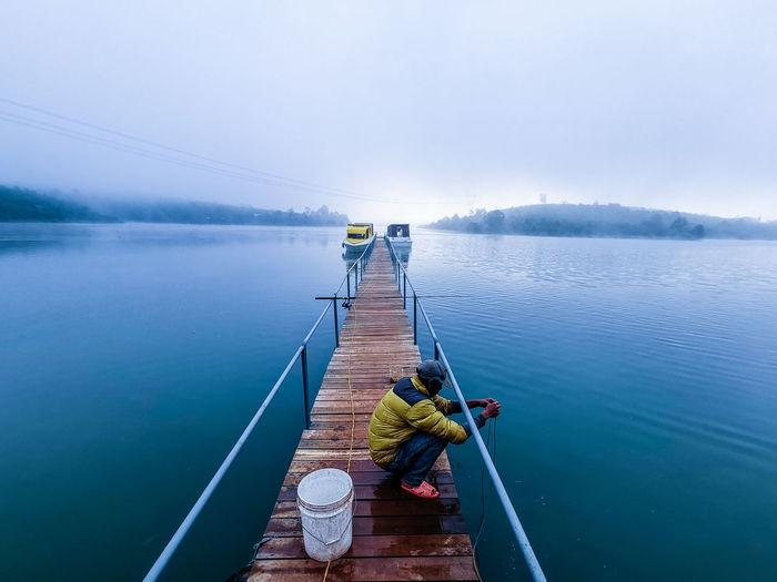 Rear view of man sitting on boat at lake