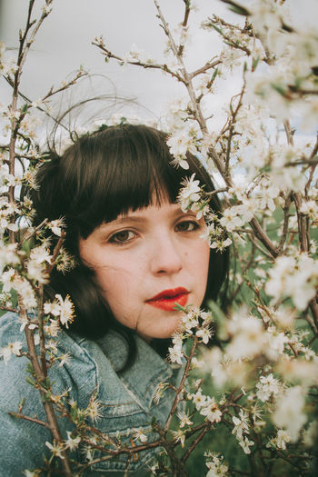 Portrait of beautiful young woman against plants